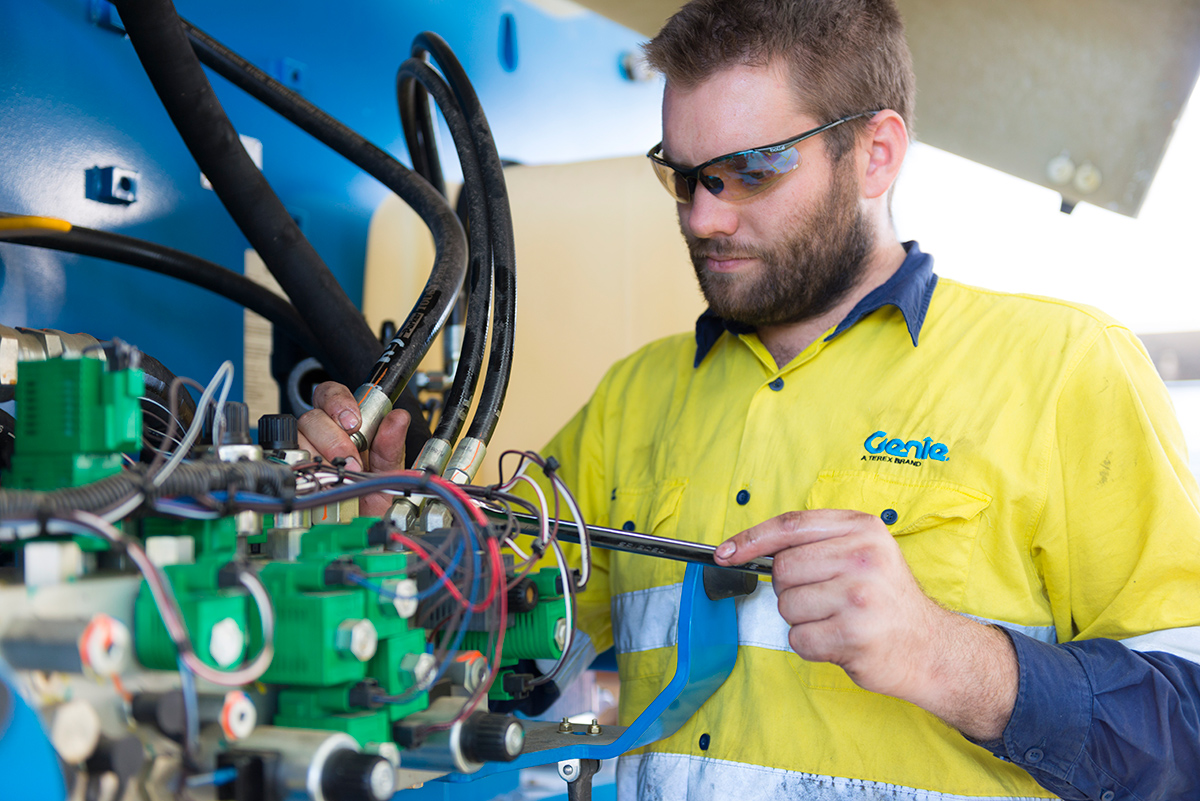 Genie service technician inspecting hydraulic hoses during scheduled maintenance